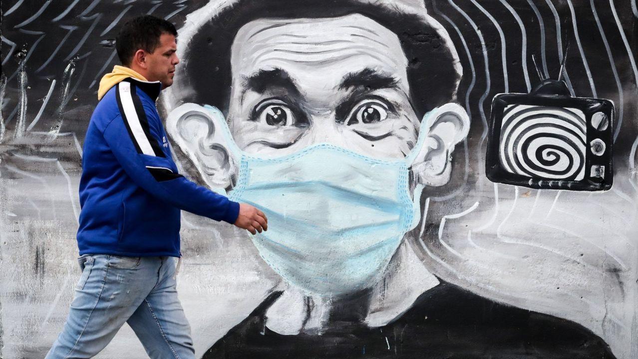 Un hombre pasando ante un grafiti del personaje don Ramón con mascarilla, en Montevideo
