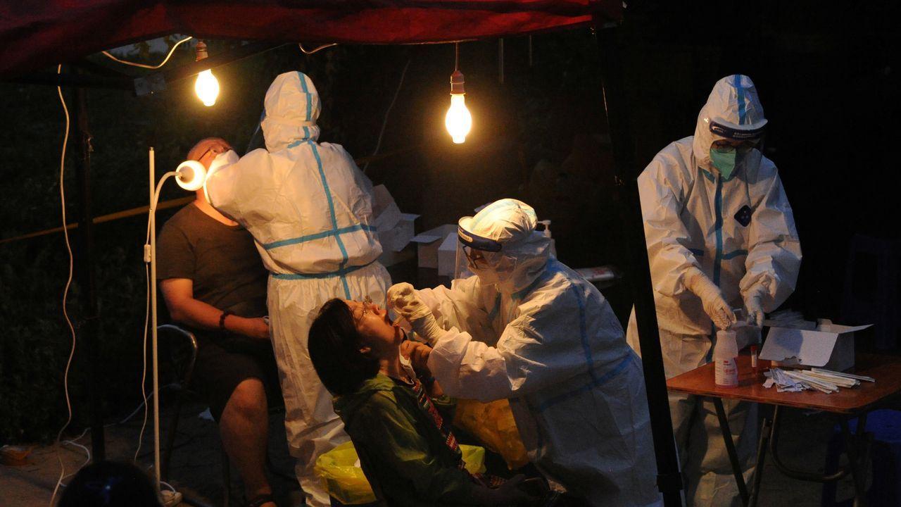 Los trabajadores con trajes protectores recogen hisopos para la prueba de ácido nucleico en un sitio de prueba improvisado, luego del brote de la enfermedad del coronavirus, en Dalian, provincia de Liaoning, China