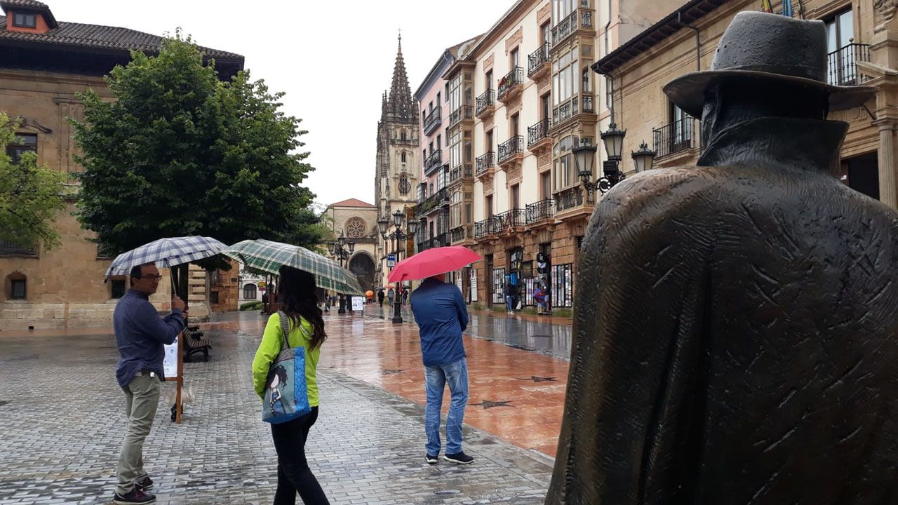 Turistas en Asturias con lluvia.Un rayo ilumina la playa de San Lorenzo, en Gijón