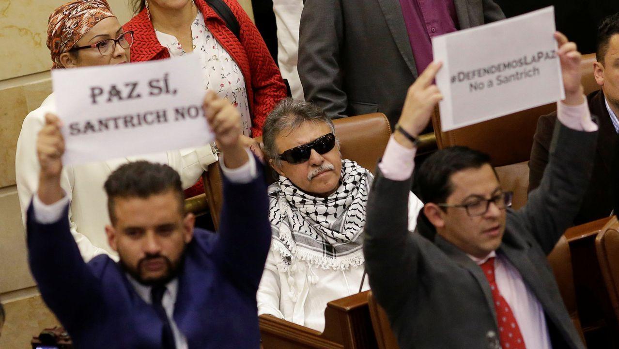 Santrich, en el centro, mientras dos parlamentarios protestan contra él en la Cámara colombiana, durante una sesión el pasado 13 de junio