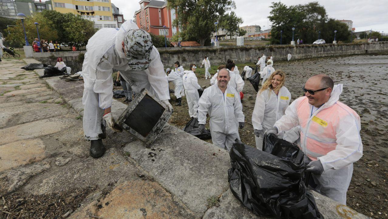 Más de un centenar de personas acuden a limpiar los fondos de la ría de O Burgo.Imagen del vehículo sumergido entre el pantalán y el muro de Bouzas