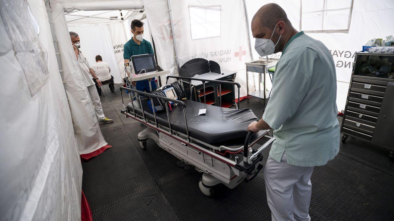 Profesionales sanitarios trasladan equipamiento diagnóstico en un hospital de campaña en Budapest