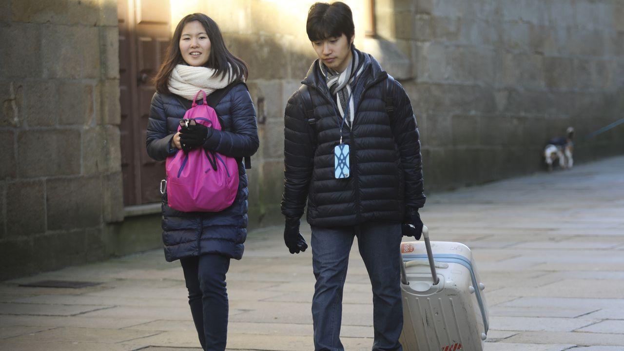 Turístas asiáticos con maletas en una calle de Santiago