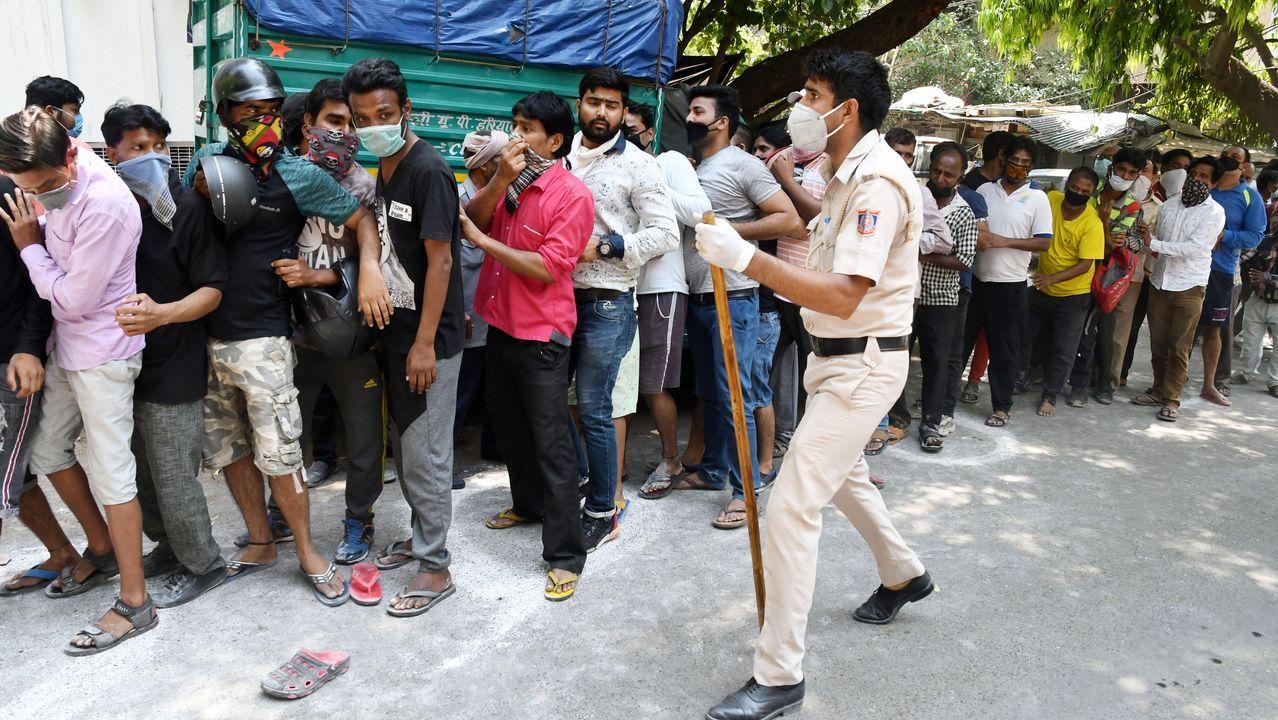 Fin de semana en tiempos de pandemia.Un policía indio se esfuerza, sin conseguirlo, en que un grupo de clientes de una licorería mantengan la distancia social