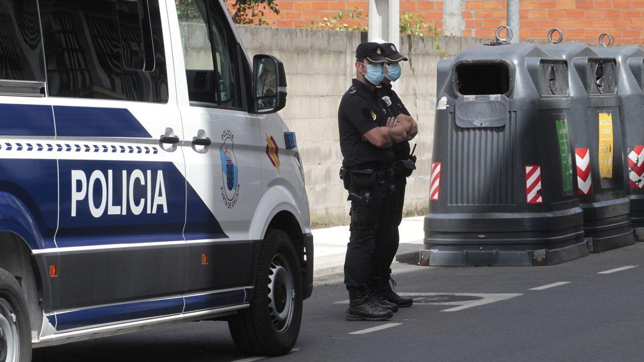 Agentes de la unidad de la Policía Nacional adscrita a la Xunta vigilan el portal del edificio confinado en Monforte