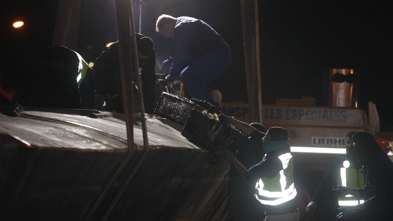Un miembro de Protección Civil realiza un corte en el casco con una radial, al parecer para poder achicar el agua interior del narcosubmarino