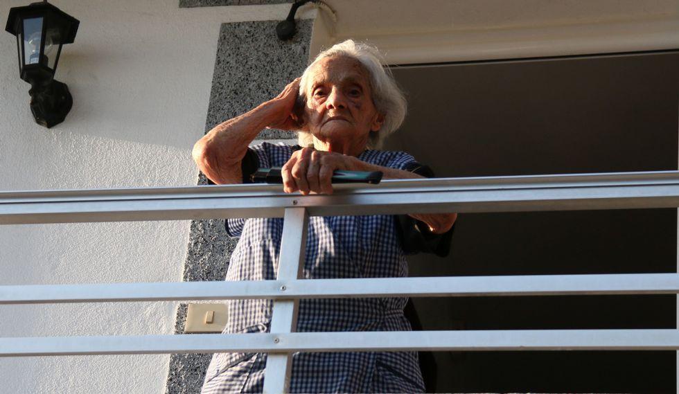 Marina agarrando el pelo que el aire le levanta en el balcón de casa.