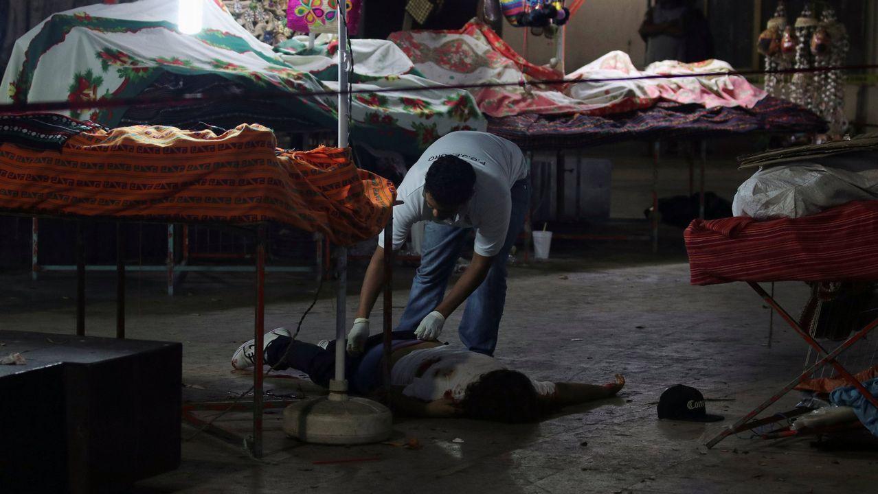 Un forense examina el cadáver de un hombr tiroteado en un mercado de Acapulco