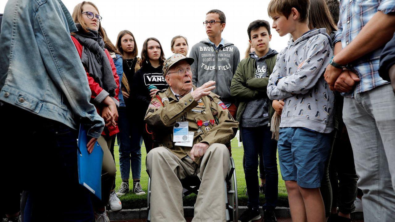 El veterano militar estadounidense George Shenkle conversa con varios jóvenes en el cementerio de los soldados caídos estadounidenses en Colleville-Sur-Mer
