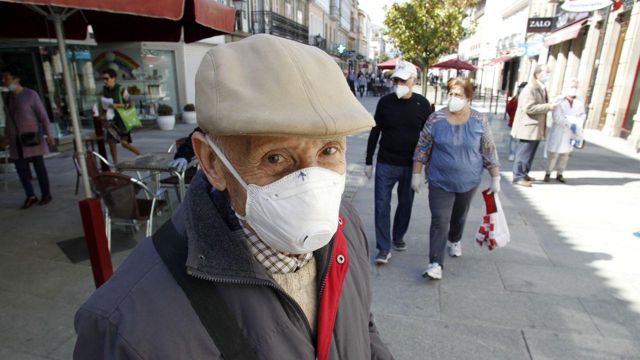 Un hombre con mascarilla hace cola para entrar en un banco este lunes en el centro de Monforte
