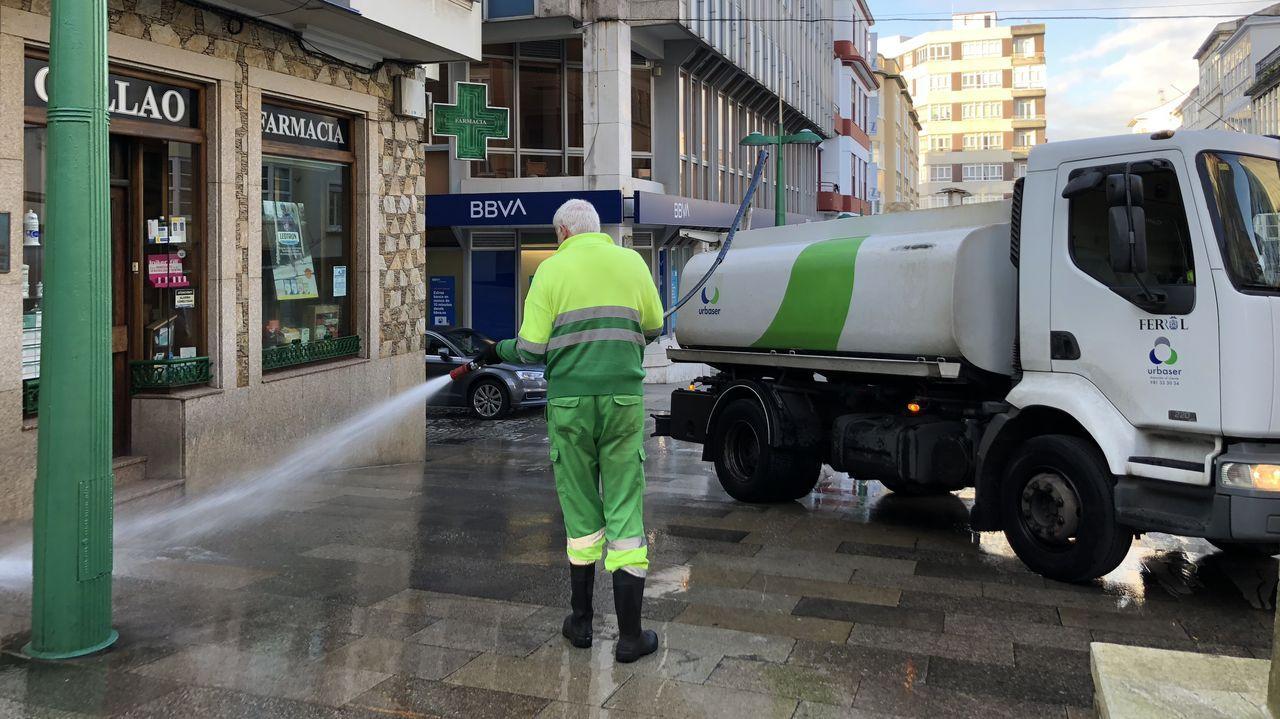 Personal de limpieza de Urbaser en Ferrol baldeando delante de la farmacia del Callao por el coronavirus