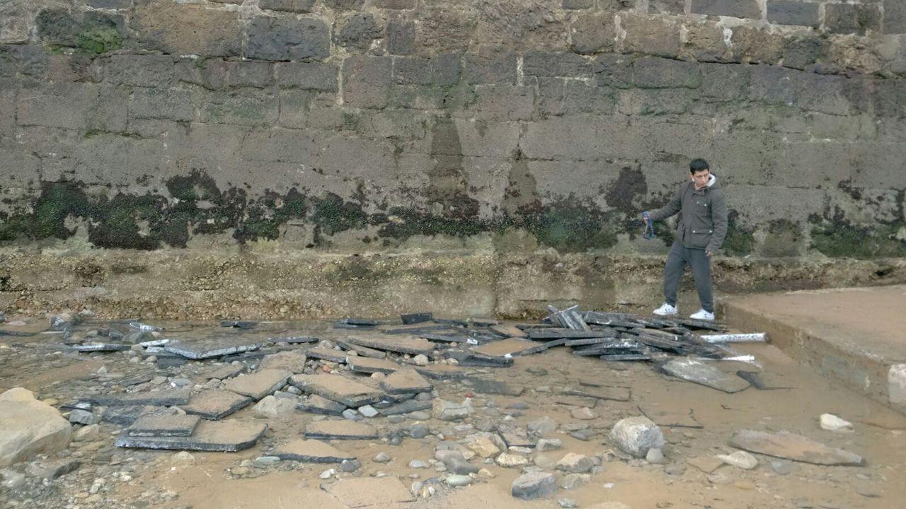 Un chico observa la falta de arena en la playa de San Lorenzo junto a la escalerona