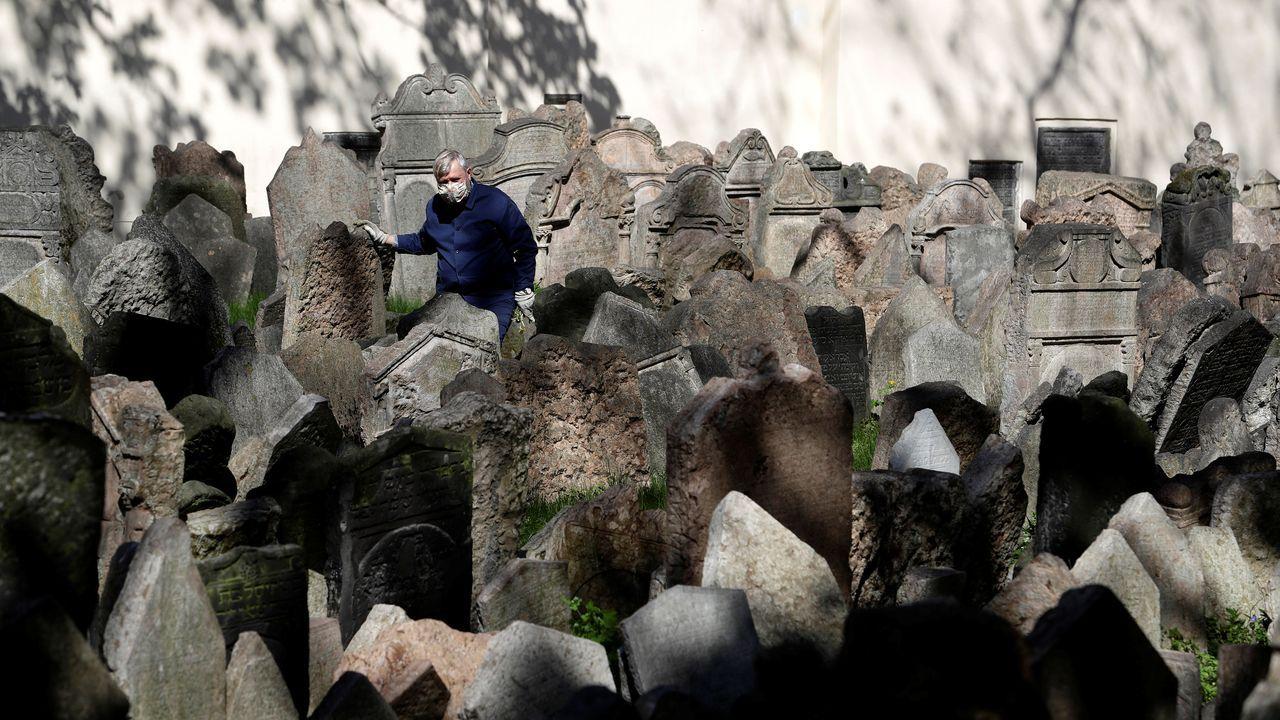 Un operario del cementerio judío de Praga, trabajando con mascarilla
