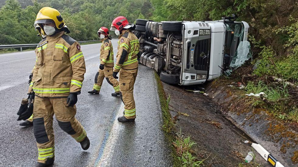 Primer adelanto de  Live is Life .Los bomberos, junto al camión accidentado este martes en la bajada desde el alto de Guítara a Os Peares