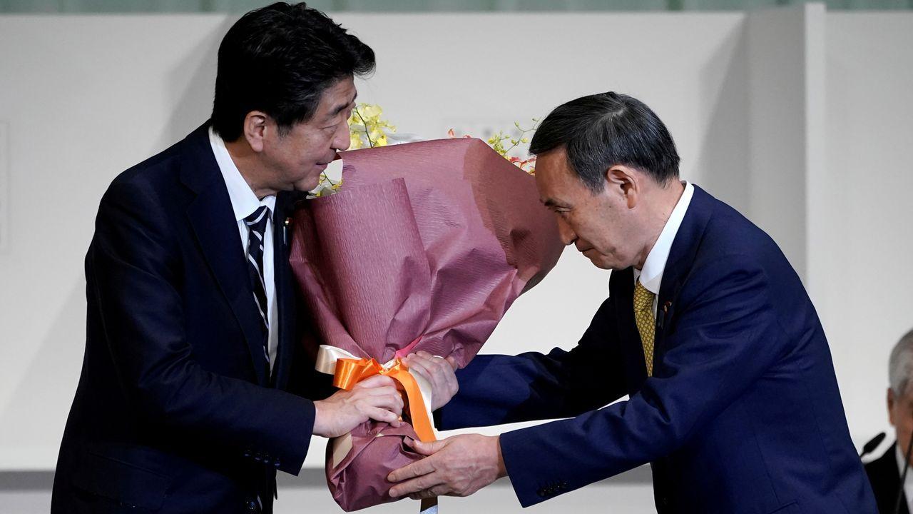 Shinzo Abe entrega un ramo de flores a su sucesor Yoshihide Suga