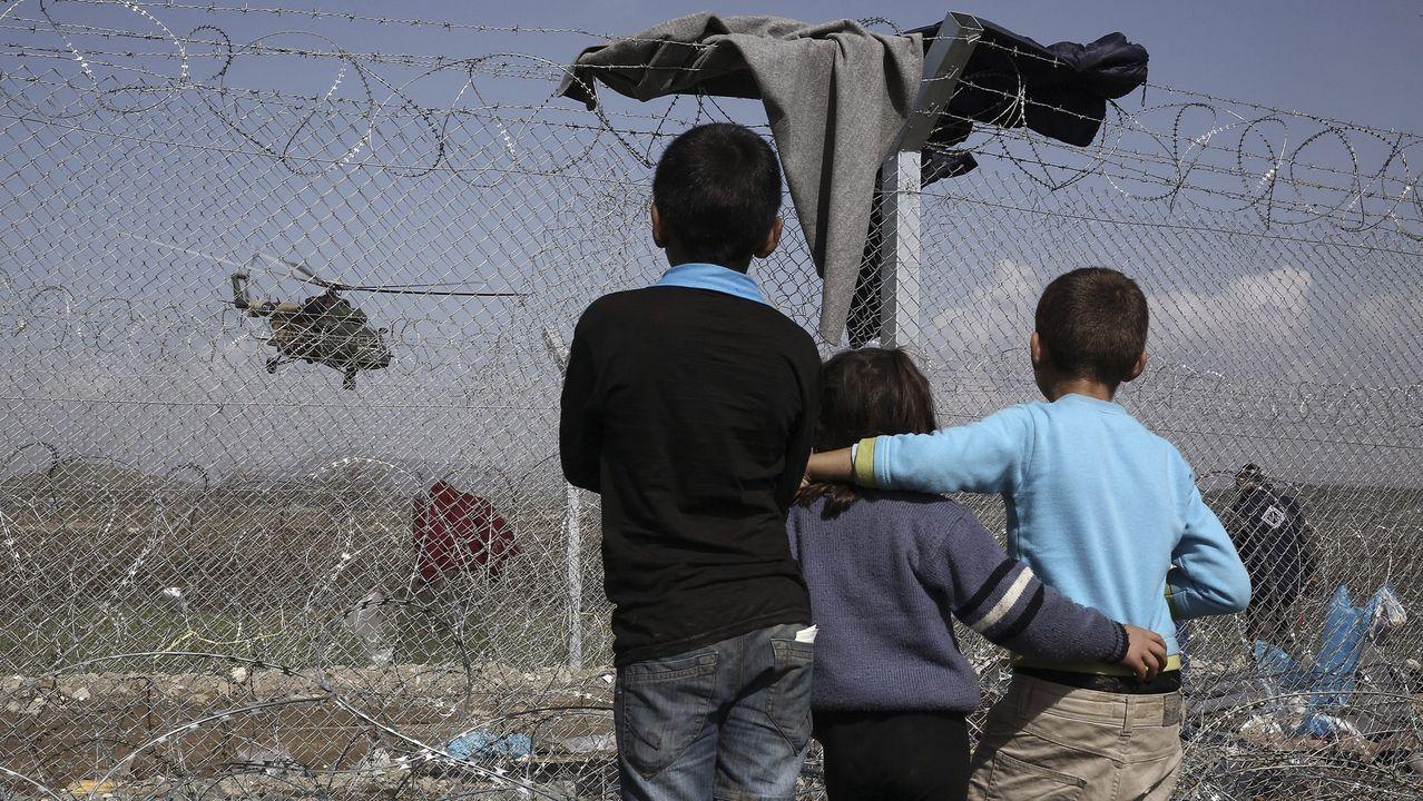 Las ilustradoras trazan Oviedo.Un grupo de niños observa un helicóptero desde un campamento de refugiados en Idomenia, Grecia