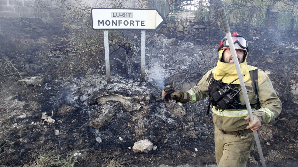 Un integrante de la brigada helitransportada del monte Marroxo, frente a una señal de tráfico en la zona afectada por uno de los dos incendios de ayer en Moreda
