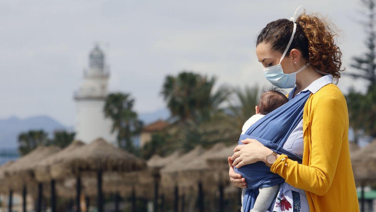 Una mujer protegida con una mascarilla da un paseo con su bebé en la playa de La Malagueta