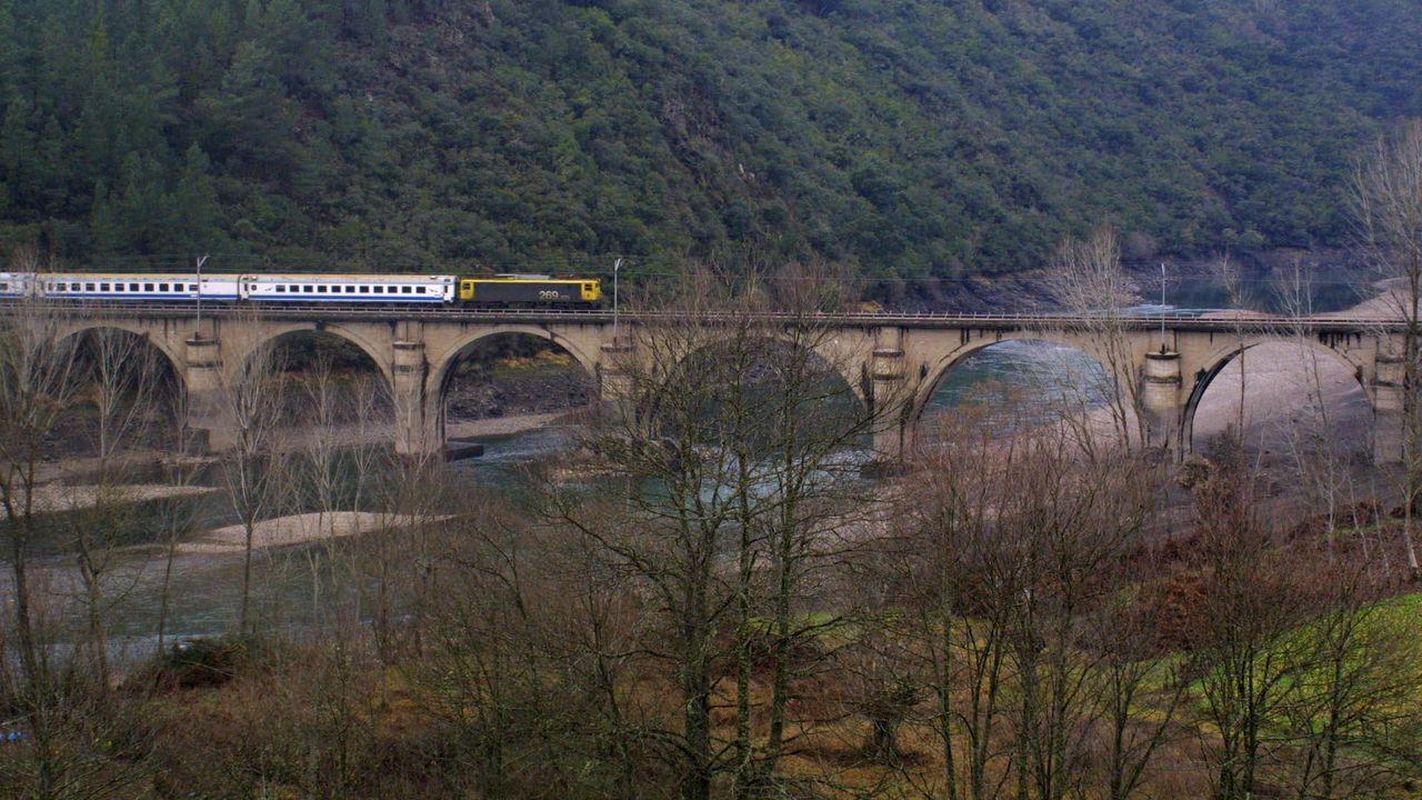 Fotografia de archivo de un tren de viajeros cruzando un puente sobre el río Sil en Rairos (Quiroga)
