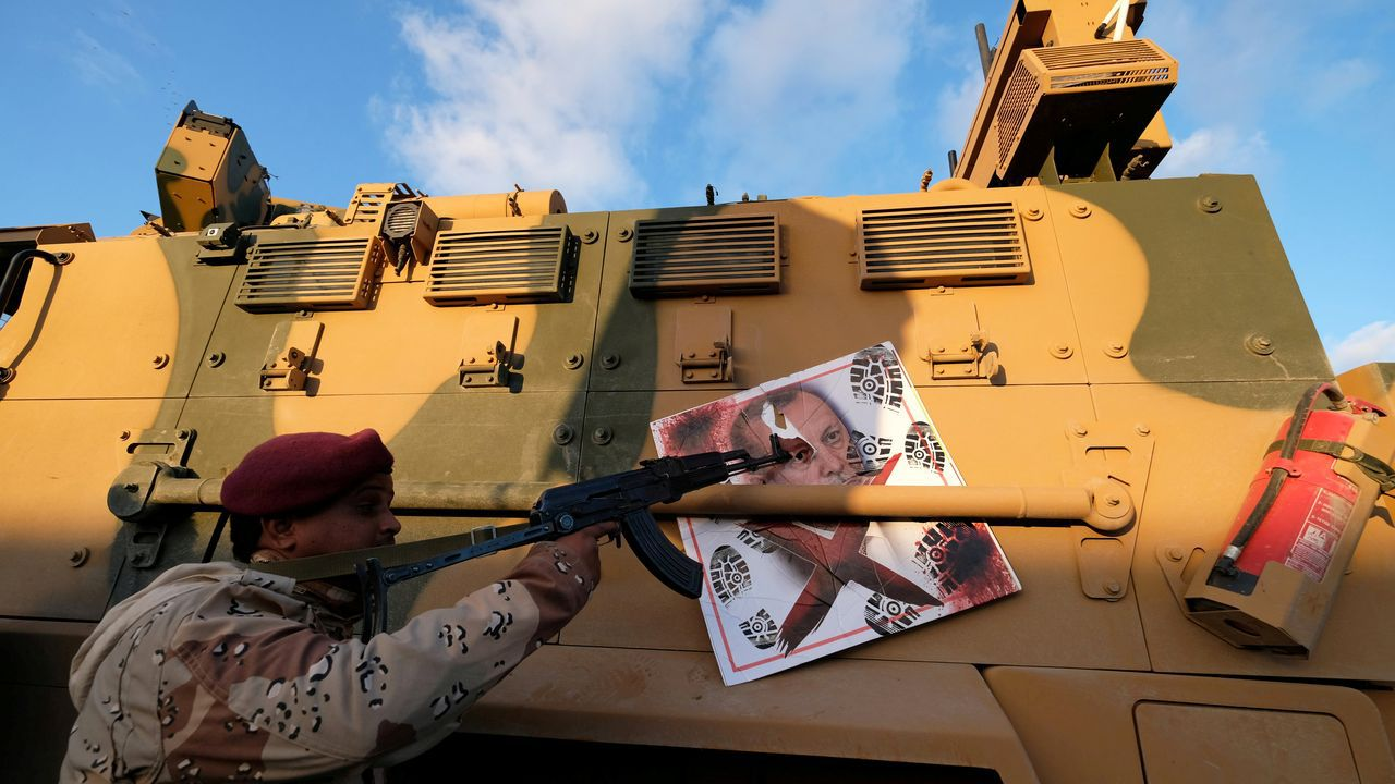 Un combatiente de las fuerzas de Haftar apunta a una imagen de Erdogan colgada de un blindado turco confiscado durante los combates en Trípoli