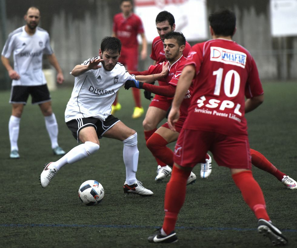 Martín despeja un balón de cabeza ante la mirada de su compañero Diego Cespón.
