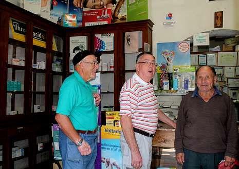 Pedro Sánchez y otros dos vecinos, en la farmacia en la que no suelen encontrar sus medicinas.