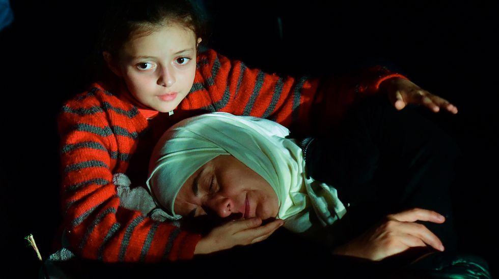 Una niña inmigrante y su madre descansan en la frontera entre Serbia y Hungría