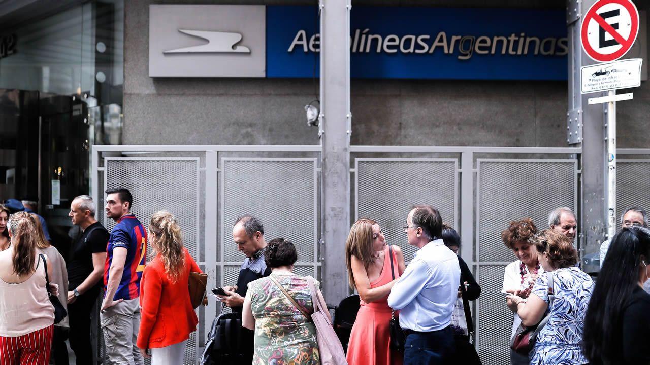 Una fila de personas espera hoy jueves 12 de marzo en las oficinas de Aerolíneas Argentinas para poder devolver los pasajes de avión con destino a Roma y Madrid