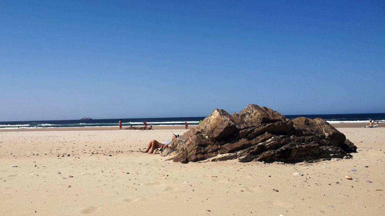 El otoño será más cálido de lo normal en Galicia.Una bañista se protege del vientro detrás de una piedra en la playa de Xagó (Gozón)