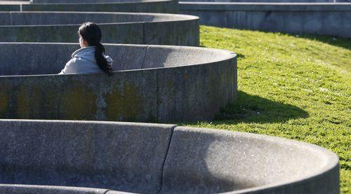 Una mujer sentada al sol en un parque de Oviedo