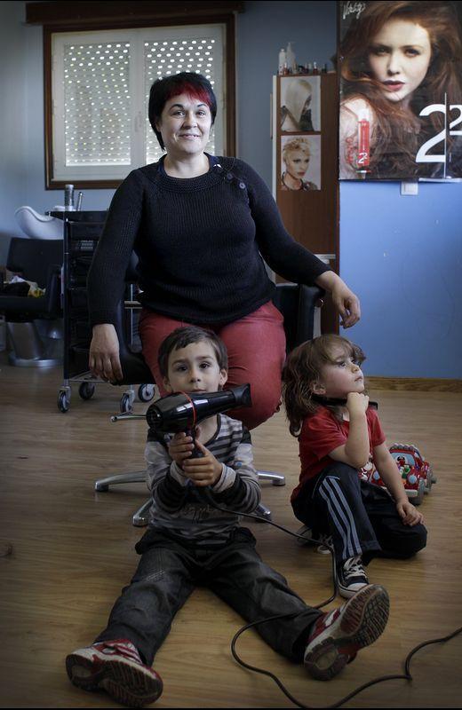 Nieves con sus dos hijos en su peluquería de Montederramo.