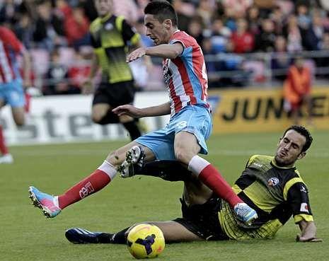 Toda la actualidad de la jornada de Segunda división.Iago Díaz, con el cuero, trata de esquivar la entrada de un futbolista del Sabadell.