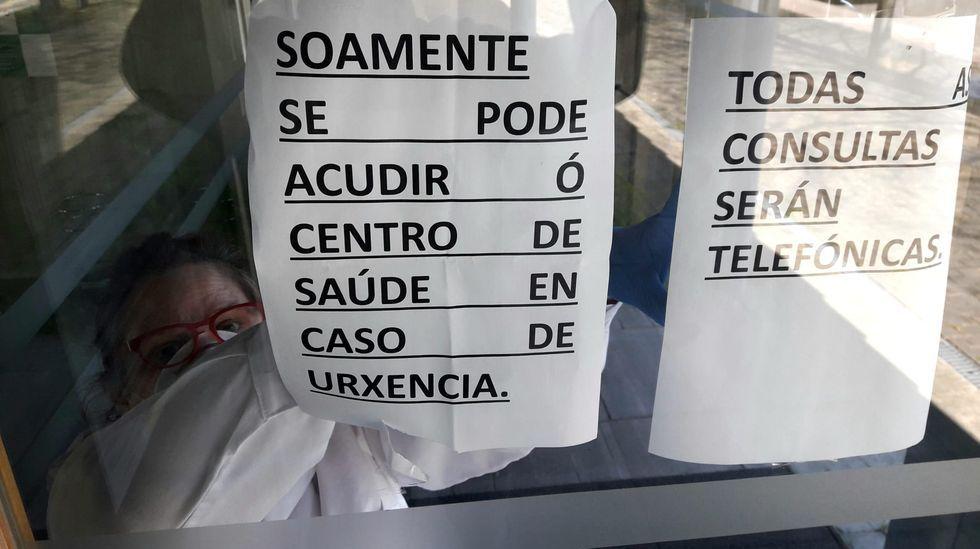 Una trabajadora sanitaria coloca los carteles a la entrada del ambulatorio de A Barrela