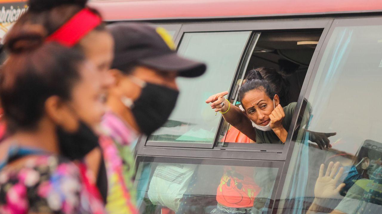 Una mujer se asoma por la ventana de un bus del operativo de retorno de desplazados venezolanos, en San Antonio del Táchira