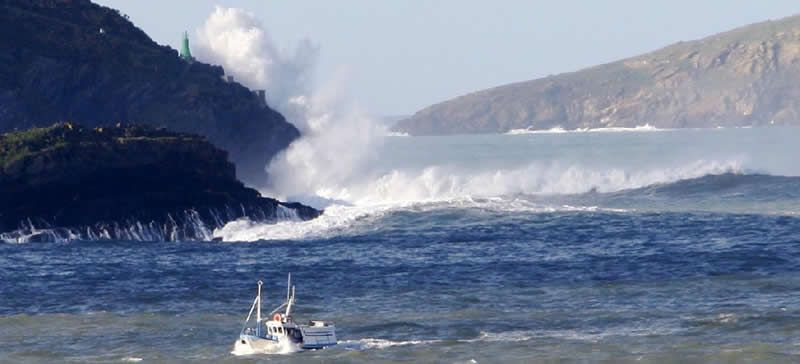 barco.Una pareja sorprendida por un golpe de mar en la playa de Esteiro, Xove