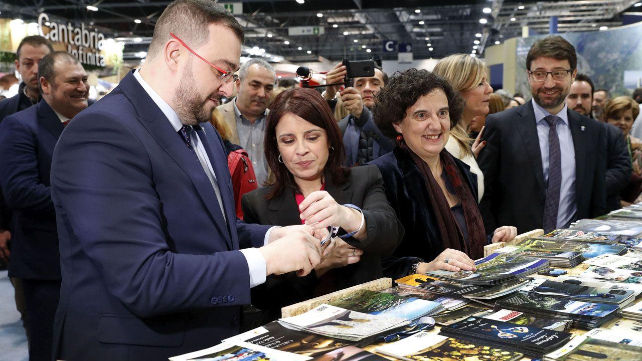 Adrián Barbón coloca a Adriana Lastra una pulsera promocional en presencia de la consejera de Cultura, Berta Piñán, de la viceconsejera de Turismo, Graciela Blanco; y del consejero de de Industria, Enrique Fernández.