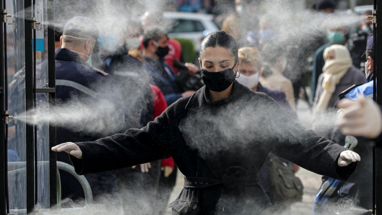 Un grupo de pasajeros consulta los vuelos en el Aeropuerto de Asturias.Una mujer es desinfectada en Tirana, Albania, antes de entrar en un supermercado