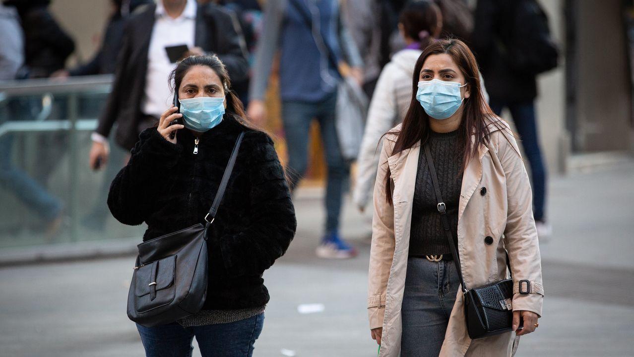 EN DIRECTO: primer positivo por coronavirus en Galicia. La consellería informa de todos los detalles.Dos mujeres con mascarillas caminan por Barcelona