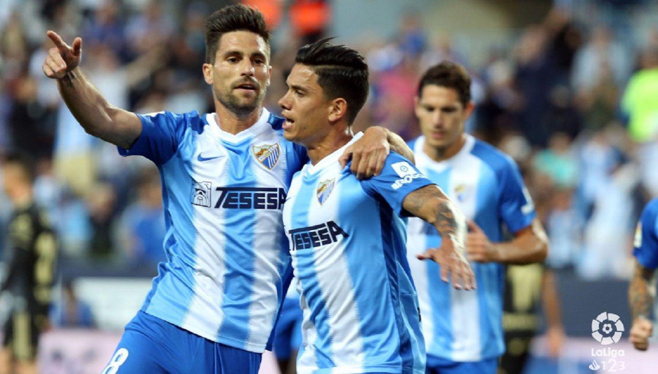 Gol Adrian Renato Santos Malaga Real Oviedo La Rosaleda.Adrián González y Renato Santos celebran el primer gol del Málaga