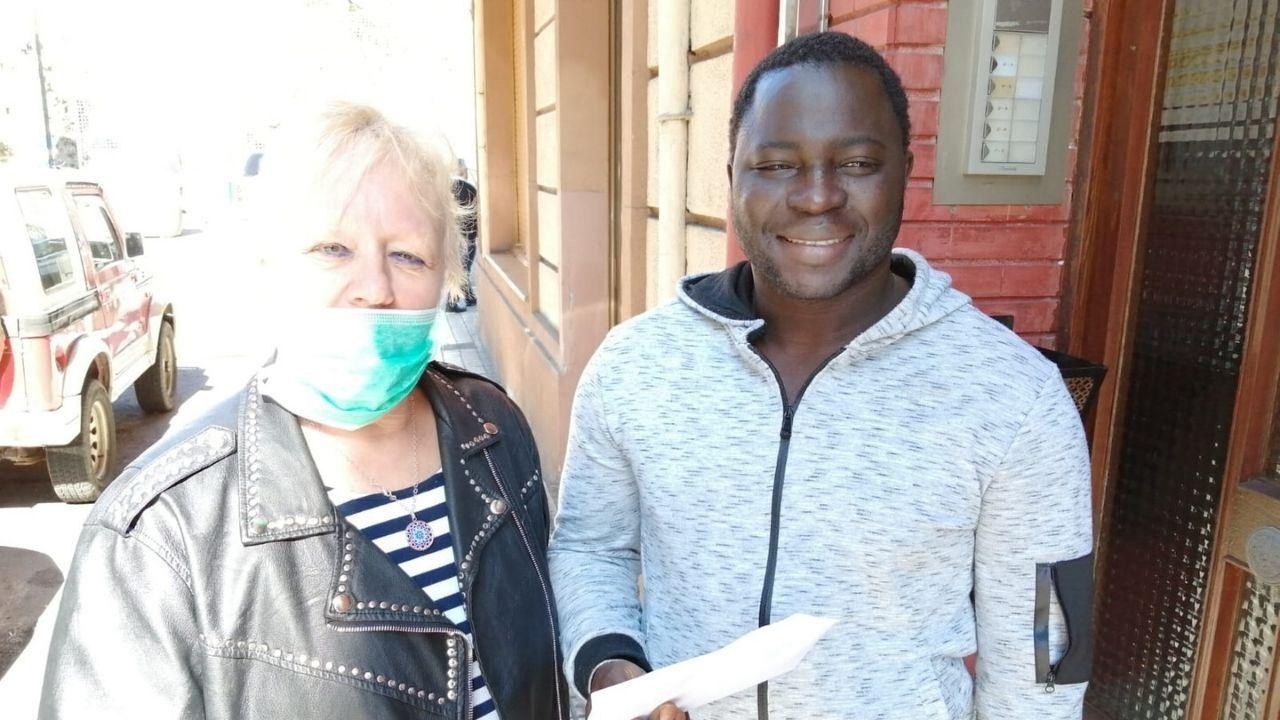 Cadena humana hostelera para repartir alimentos.María Luisa, parte del equipo de Intervalo, entrega uno de los vales de comida a Adama, inmigrante residente en Langreo