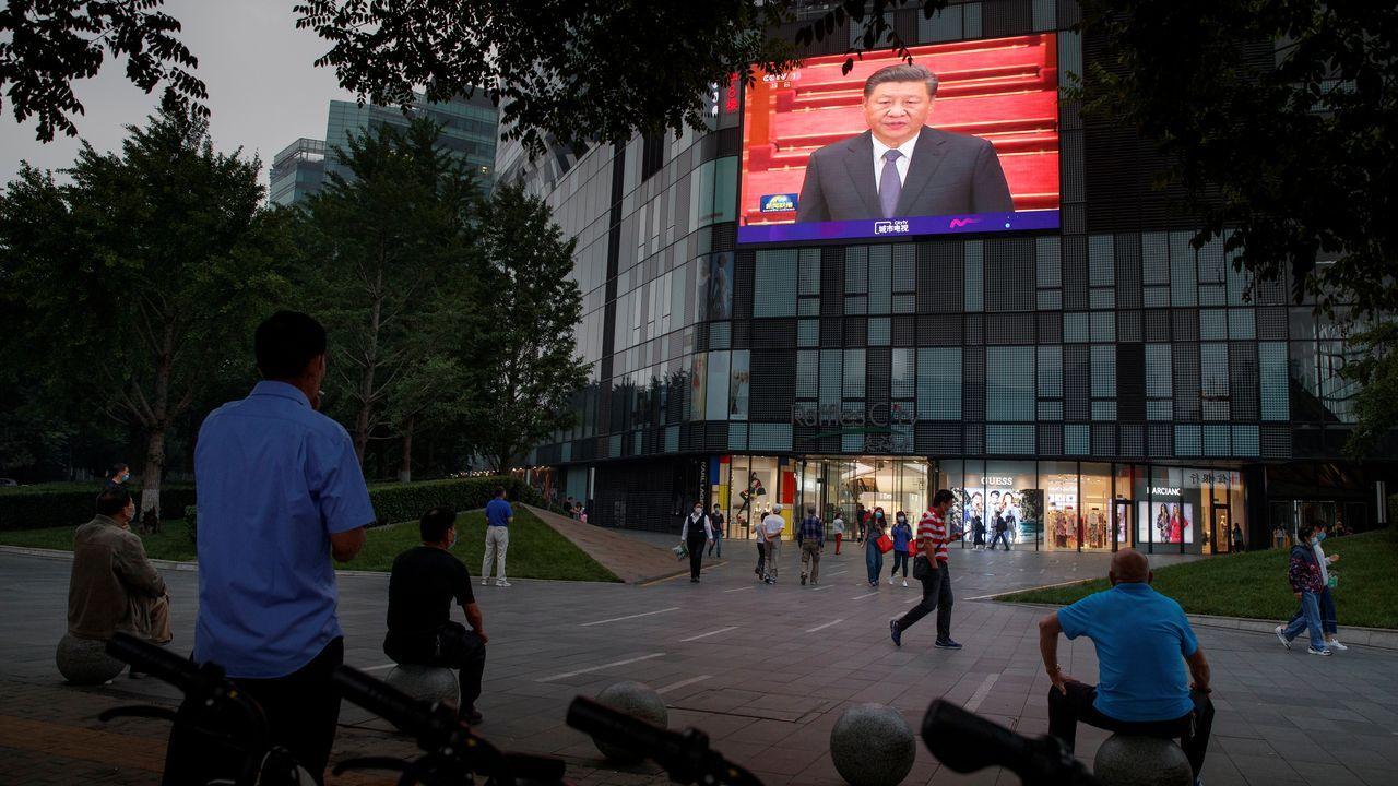 Los chinos observan, hoy, al presidente del país, XiJinping, en la retransmisión en las calles de la Conferencia Política Consultiva del Pueblo en el Gran Palacio del Pueblo en Pekín