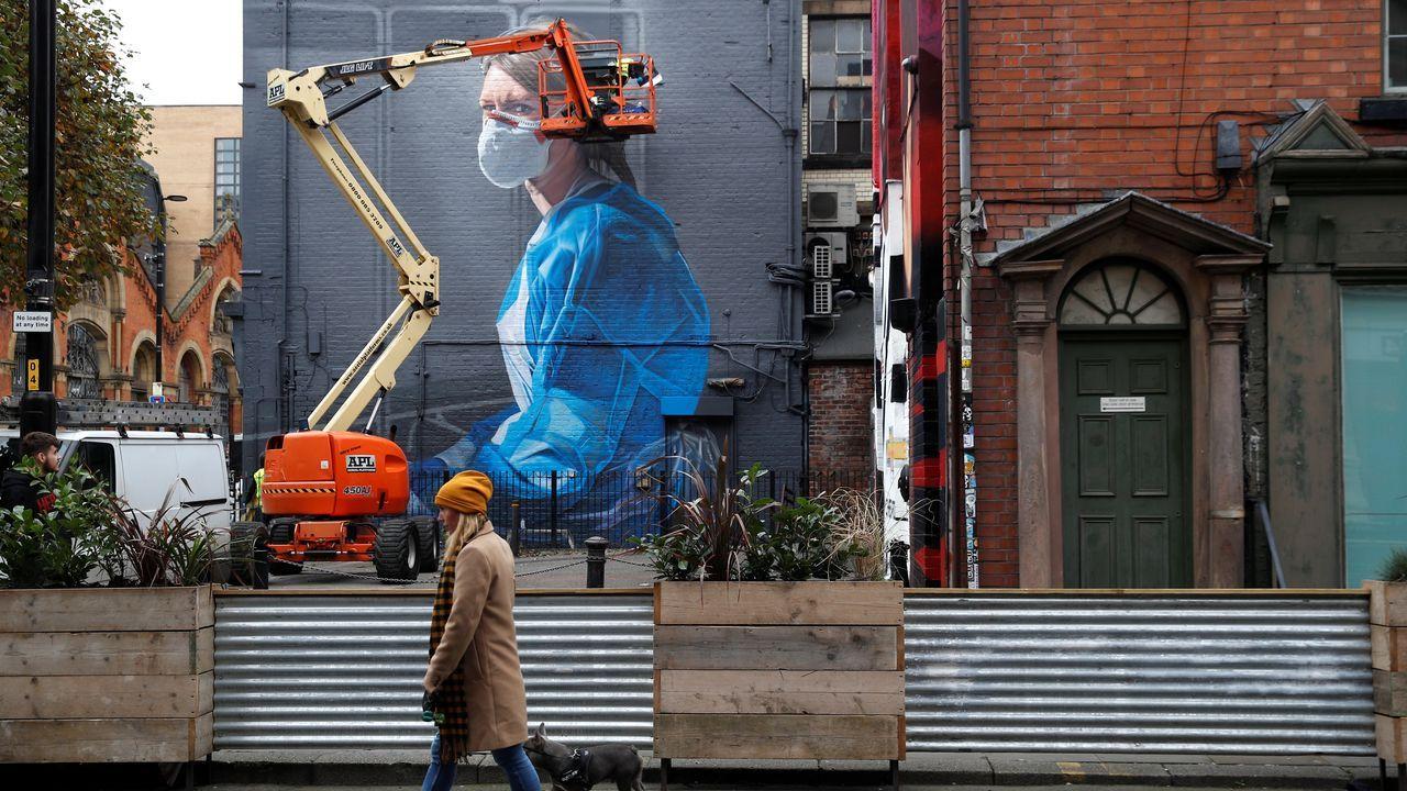 Un artista trabaja en Manchester en un mural sobre el coronavirus
