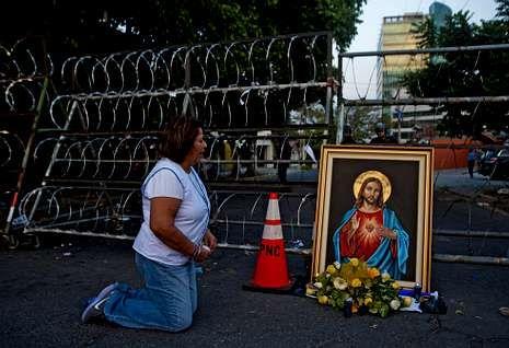 Retenidos por mafias de la inmigración.Una seguidora de la derechista Arena reza frente al Tribunal Supremo Electoral.