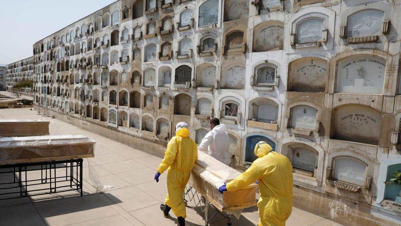 Sepultureros transportan el ataud de un fallecido por coronavirus en Lima
