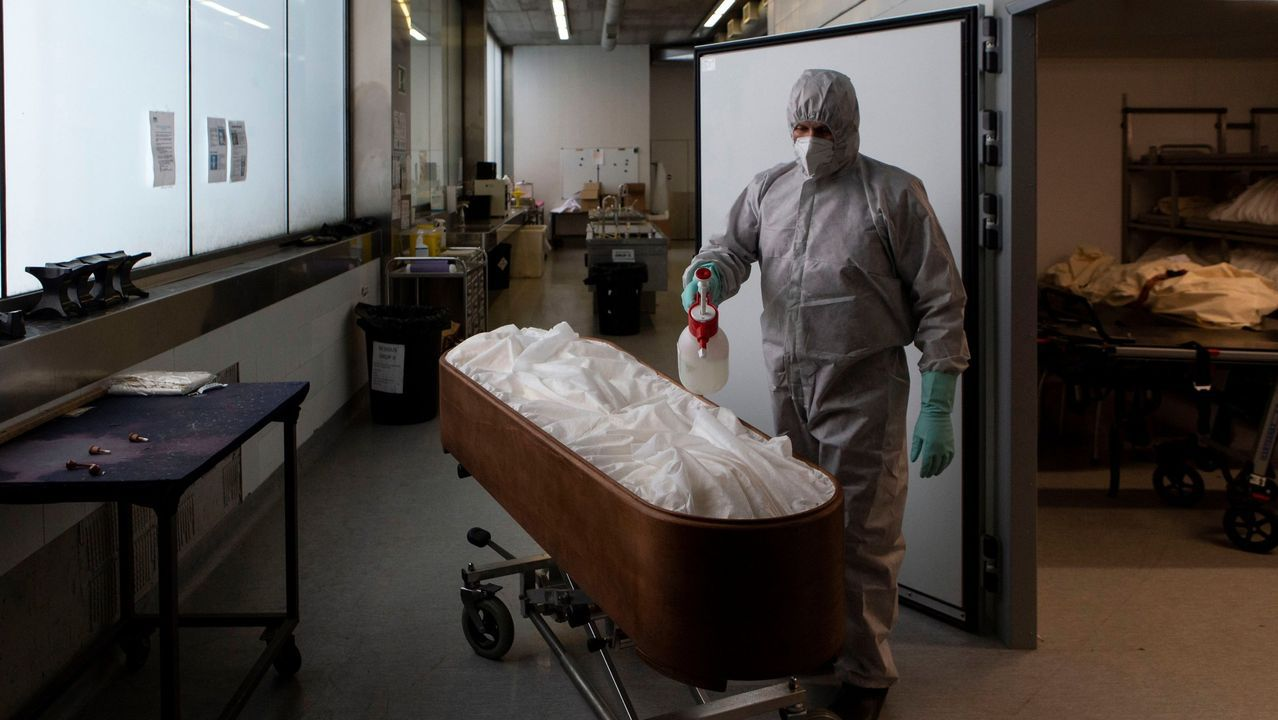 Un trabajador de una funeraria desinfecta el cuerpo de una persona fallecida con coronavirus