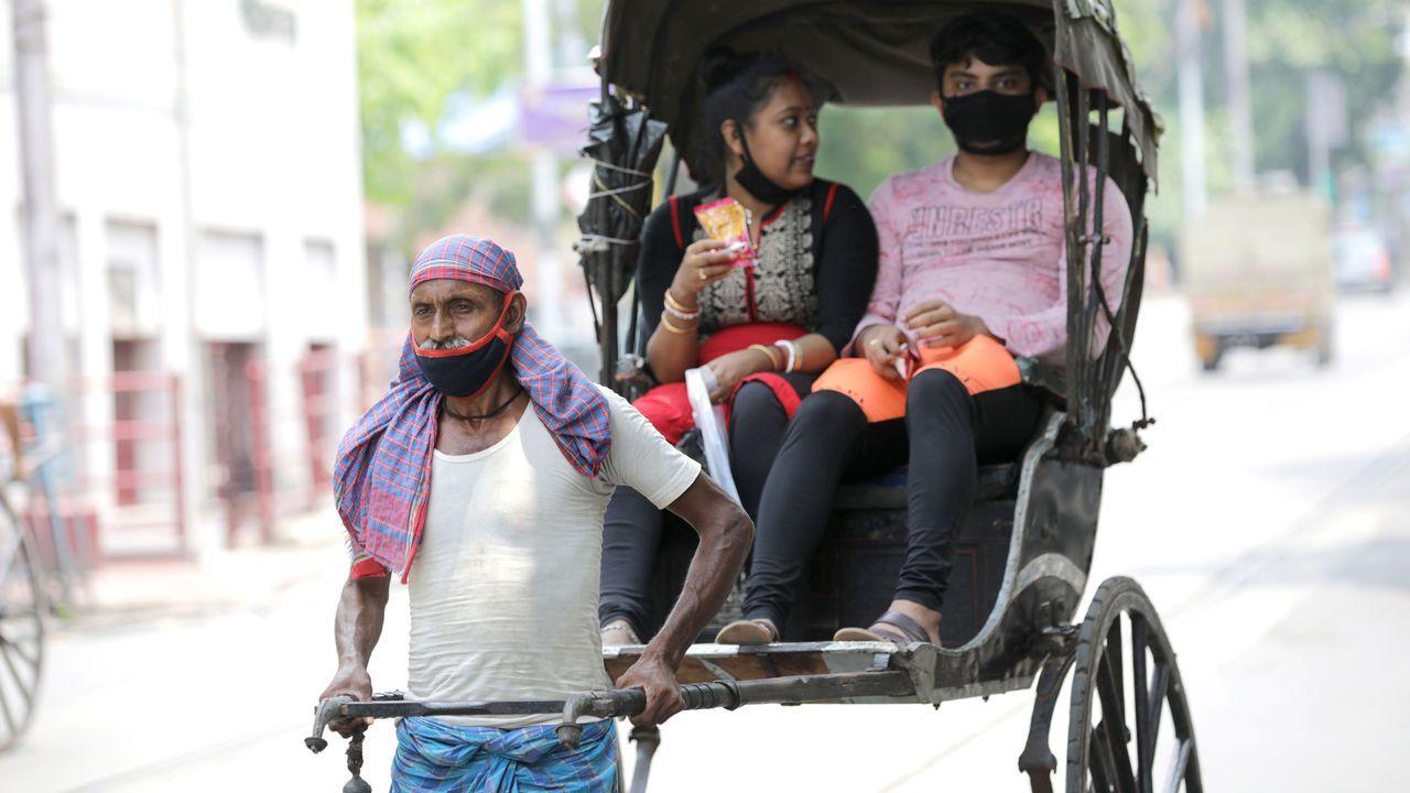 En Calcuta, un hombre ataviado con mascarilla tira de un rickshaws