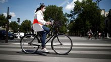 Una mujer en bicicleta y con mascarilla por París