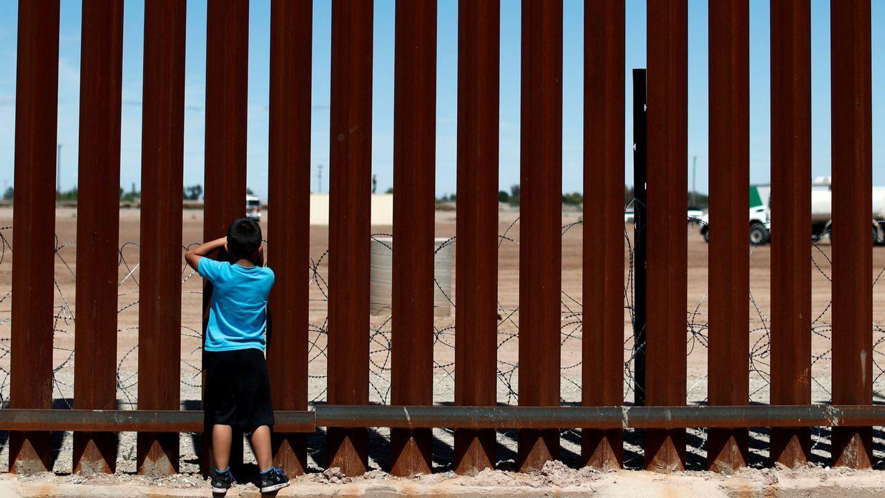 Un niño mexicano mira a través del muro que separa a su país de Estados Unidos en Calexico (California)