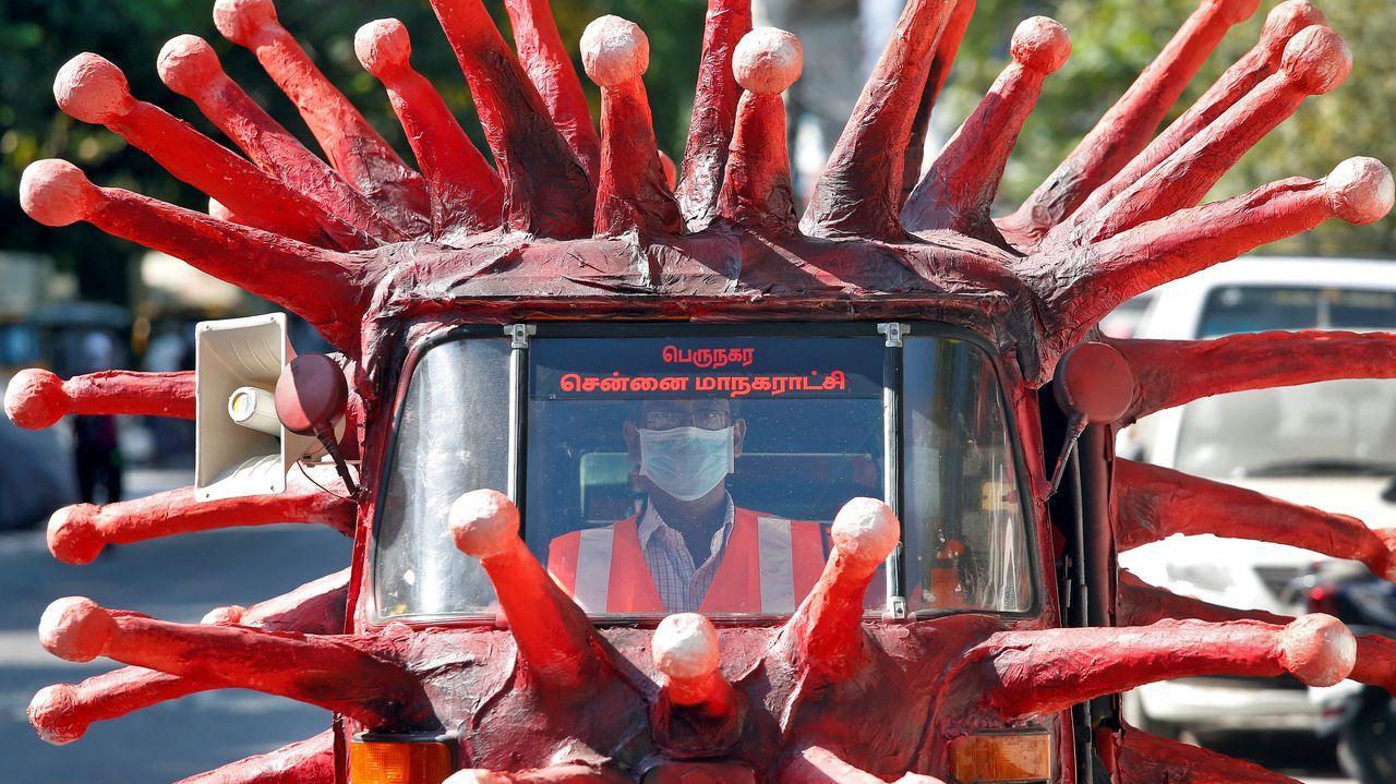 Un hombre conduce un vehículo que simula un viros para alertar de la peligrosidad del coronavirus en La India