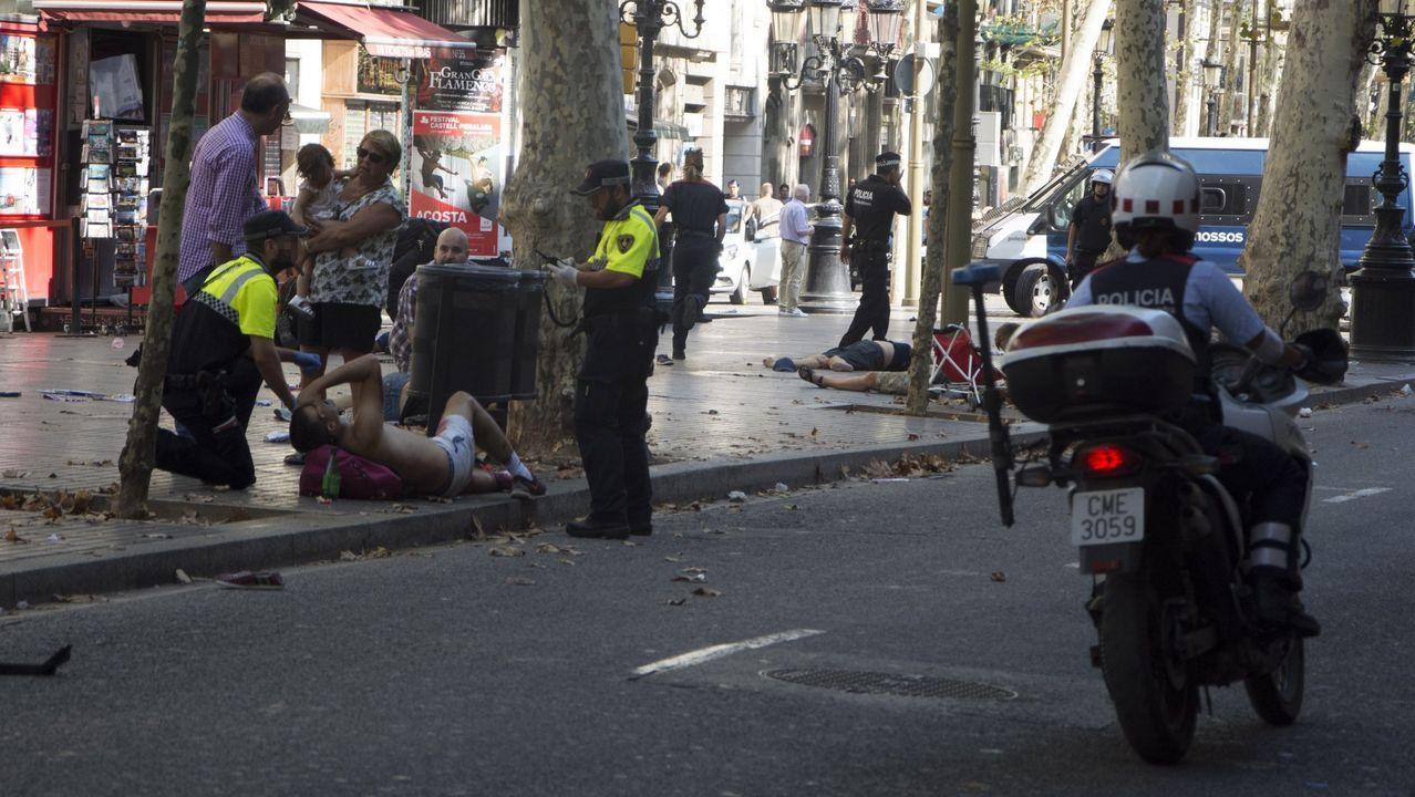 Agentes de la policía municipal de Barcelona atienden a uno de los heridos en el atentado en la Rambla